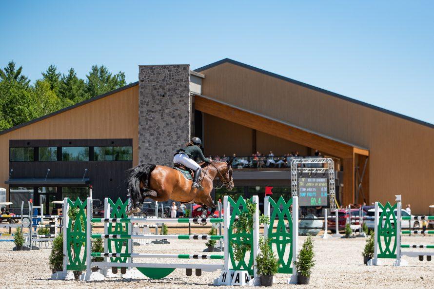 Billie Derouet in front indoor ring with Café Bistro l_Equestria and terrasse - Copie
